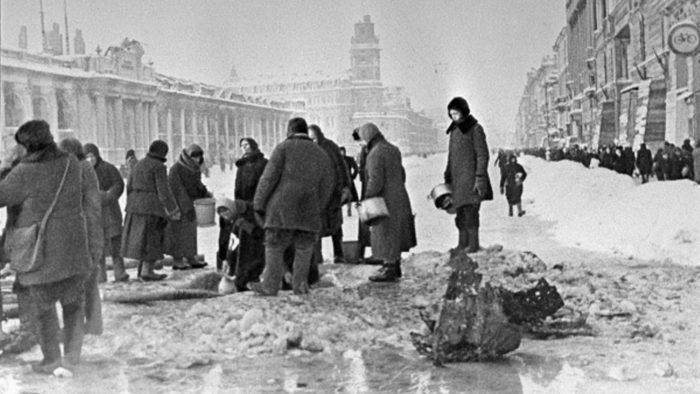 Рис. 3. Жители блокадного Ленинграда набирают воду, появившуюся после артобстрела в пробоинах в асфальте